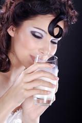 Hübsche Frau trinkt schmunzelnd Milch, Augen zu, hoch