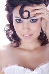 Hübsche Frau mit Löckchen lächelt mit Hand an der Stirn, hoch