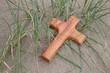 Holzkreuz am Strand unter Gräsern