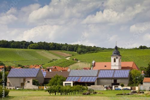 Leinwandbild Motiv Solaranlagen auf den Dächern einer kleinen Ortschaft