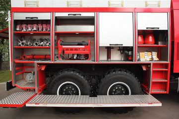 Open big fire engine equipped with fire cocks and hoses