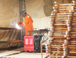 Worker in orange clothes weld metal gratings