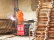 Worker in orange clothes weld metal gratings
