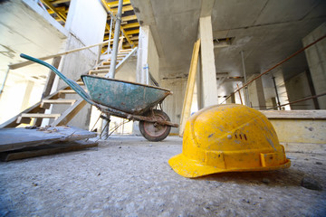 Yellow hard hats and small cart on concrete floor