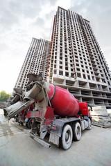 Concrete mixer stands near buildings