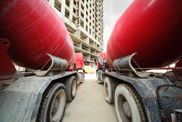 Between two concrete mixer standing near unfinished building