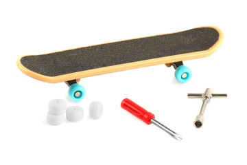 Black skateboard with yellow edge and blue wheel near tools