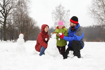 Family from three persons plays in park in winter