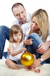Father, mother and little daughter that holds big christmas ball