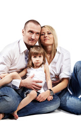 Family in white shirts and blue jeans sits on the floor.