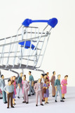 miniature toy people stand in different poses near shopping cart