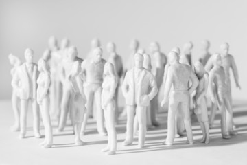 white miniature toy people stand in different poses
