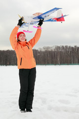 woman in orange jacket played with airplane at winter