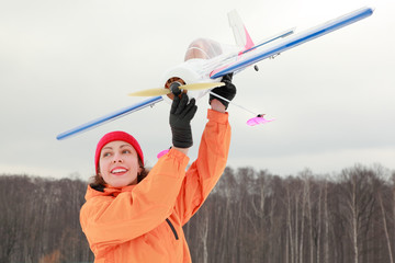 young woman in orange jacket played with airplane