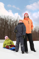 young mother, little son and daughter standing on snow