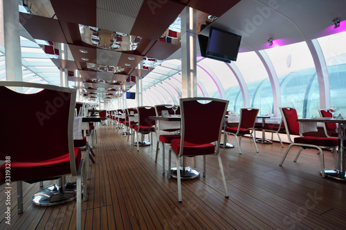 Light restaurant on board of ship, rows of tables and red chairs