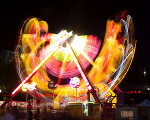Light trail blur of amusement park fairground ride at night