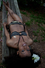 lovely black woman outside laying down in swimsuit