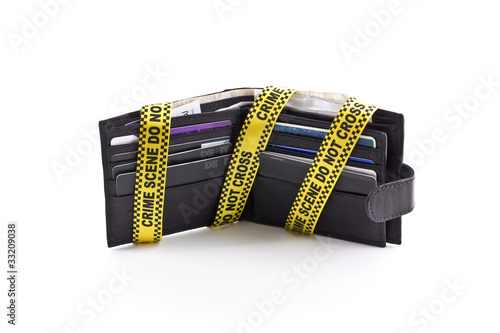 Wallet open with crime scene tape around it, isolated on a white