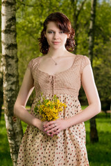 portrait of smiling caucasian girl with yellow flowers standing