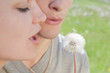 Girl and man are blowing on white dandelion