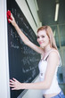 pretty, young college student erasing the chalkboard/blackboard