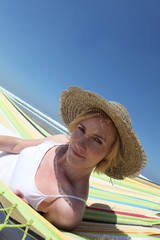 Woman wearing a straw hat lounging on a hammock by the beach