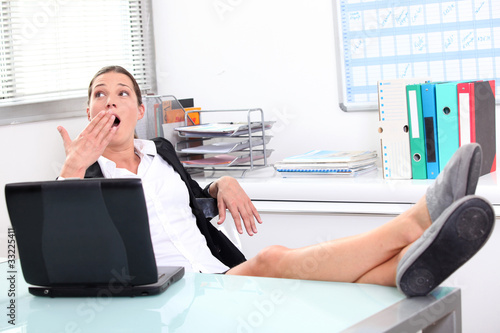 Young woman yawning in front of laptop