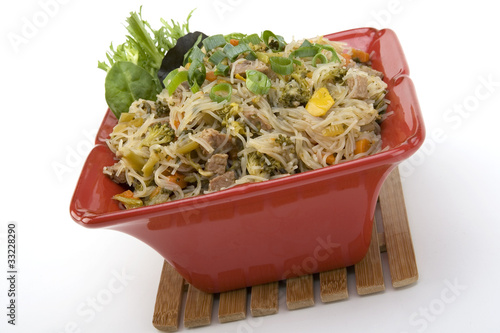 Pancit in a red ceramic dish