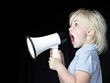 Cute blond girl shouting through megaphone