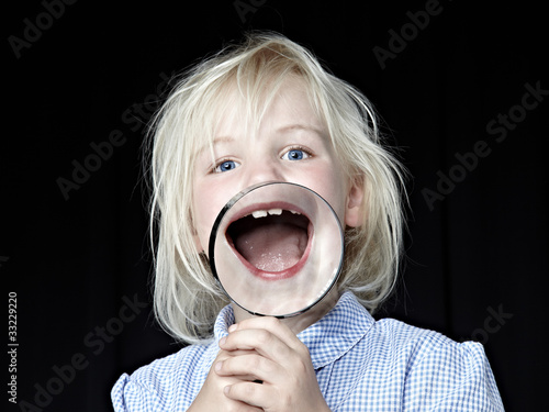 Blond girl laughing with magnifier in front of her open mouth