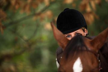 A horseback rider peeking over her horse