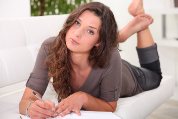 Young woman lying on a sofa writing in a journal