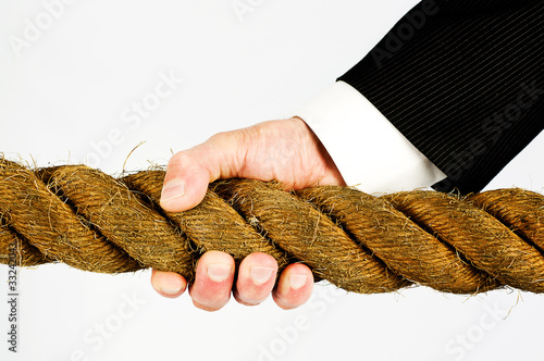 businessman hand gripping rope