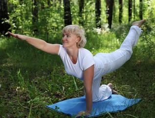 An elderly woman practices yoga