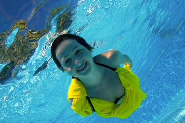 Attractive young girl diving at swimming pool.