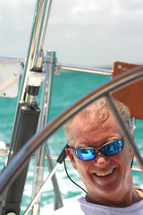 Middle-aged man steering sailboat