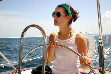 Pretty young woman steering sailboat