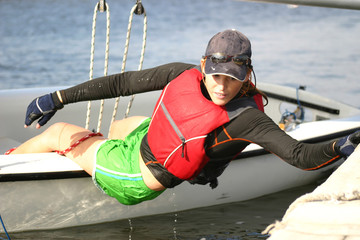 Young woman dinghy sailing at regatta