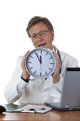 Gestresster Arzt am Schreibtisch hält Uhr und klagt über Zeitnot