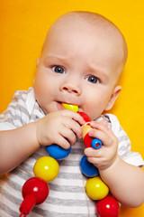 Baby kaut an Spielzeugkette