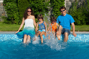 Family vacation. Parents with two kids near swimming pool