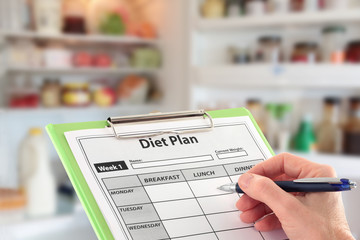 Hand Writing a Diet Plan in front of an open Fridge