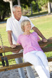 Happy Senior Couple Smiling Outside in Sunshine on Park Swing