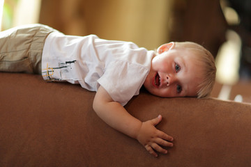 Child rests on back of sofa