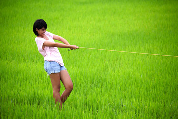 Beutiful young girl pulling yellow rope in paddy field