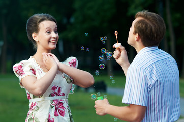 happy couple blowing soap bubbles