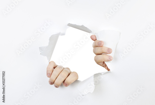 Hands ripping through hole in paper