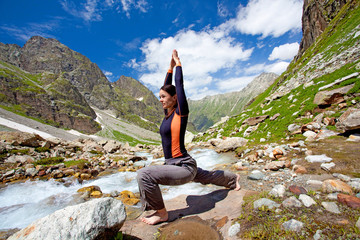 Woman is doing yogastic excersises in the mountains