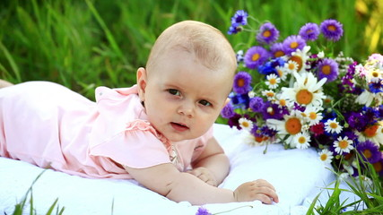 Baby in the grass with flowers. His turned at camera.